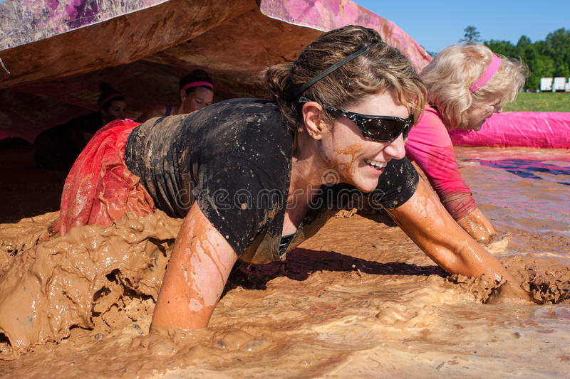 Rastejamento das mulheres com a corrida da lama de Muddy Water At Dirty Girl foto de stock