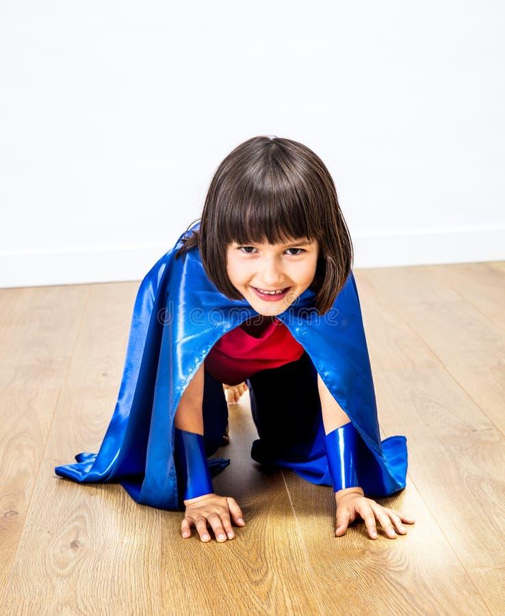 Rastejamento de sorriso da menina do super-herói, infância do divertimento ou poder fêmea foto de stock
