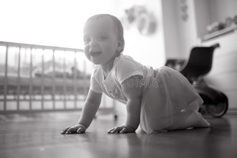 Rastejamentos e sorrisos da menina da criança no berçário fotos de stock royalty free