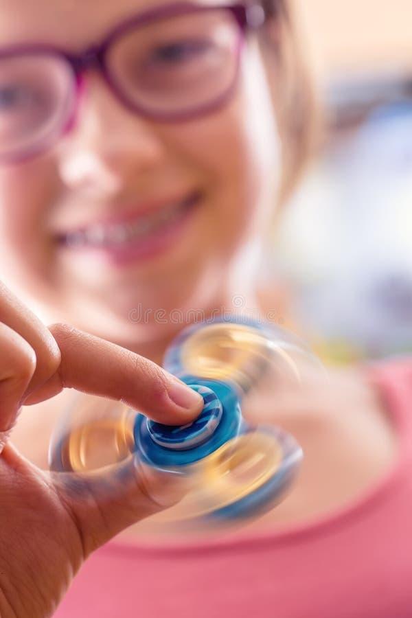 Rastlös människaspinnare Gullig ung flicka som spelar med rastlös människaspinnaren royaltyfri foto