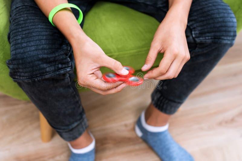 Rastlös människaspinnare Röd handspinnare, nervöst skruva på sig handleksak som roterar på handen för barn` s Spänningslättnad An arkivbilder