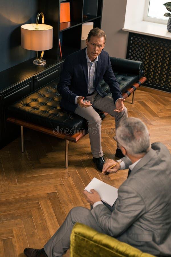 Rastlös patient som framme sitter av hans psykoanalytiker royaltyfria bilder