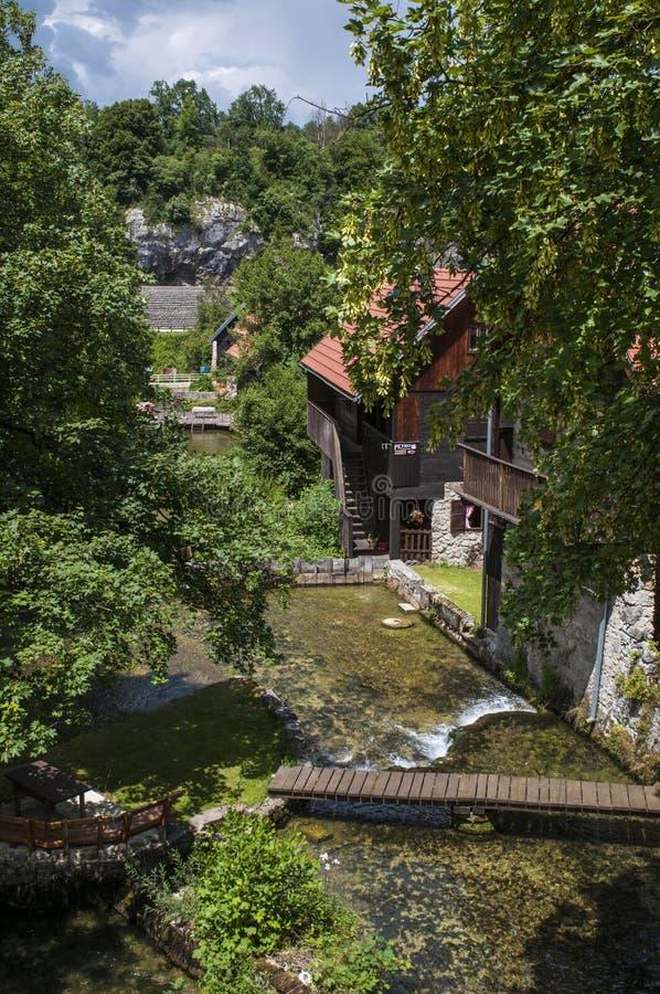 Rastoke Plitvice sjöar område, vattenfallet, Kroatien, Europa, vatten maler, floden, trähus, landskapet, horisont, gräsplan royaltyfria foton