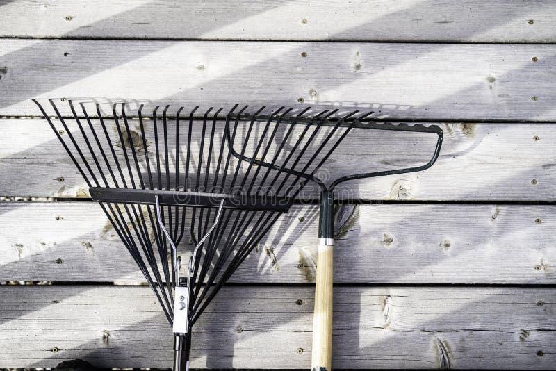Rastrillos de jardín en el decking de madera en un hogar residencial foto de archivo