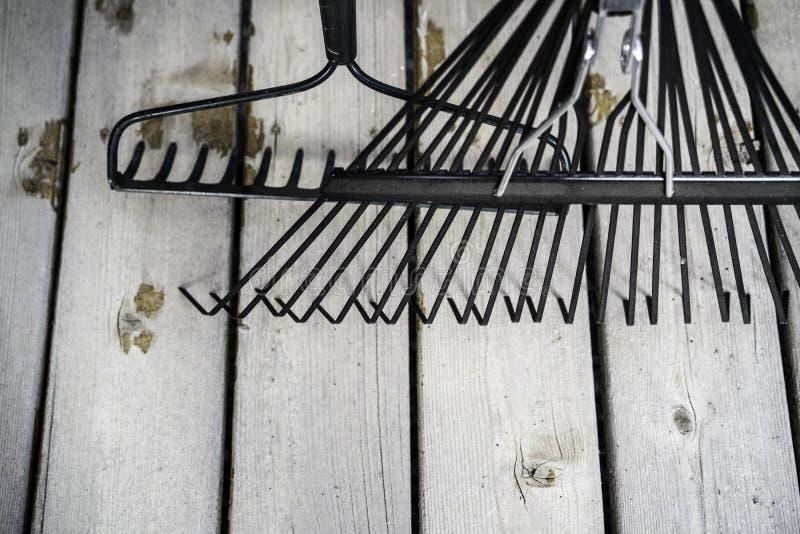 Rastrillos de jard?n en el decking de madera en un hogar residencial fotos de archivo