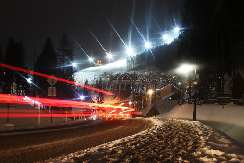 Rastro anaranjado del coche en la montaña en la noche con la cuesta imagenes de archivo