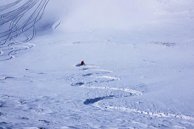 Rastro de esquiador que entra abajo en nieve fresca fotos de archivo
