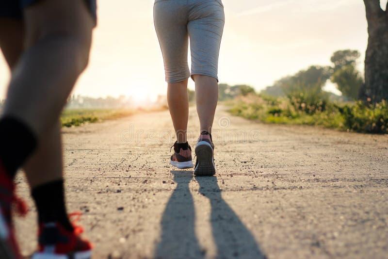 Rastro de la mujer de la aptitud de los jóvenes que corre en el camino rural en verano fotos de archivo libres de regalías