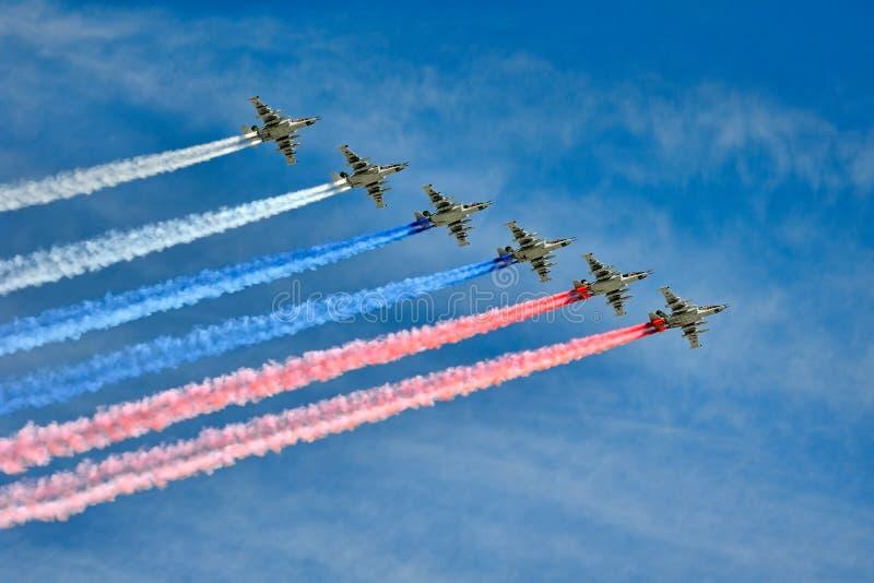 Rastro de los aviones de combate Su-25 en los colores de la bandera rusa imagenes de archivo