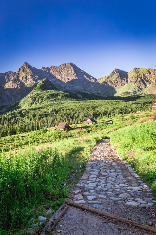 Rastro de montaña imponente que lleva a un pequeño pueblo, Polonia fotografía de archivo