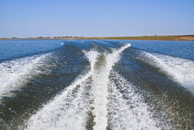 Rastro de un barco en el agua El barco de motor hizo espuma el agua con él fotos de archivo