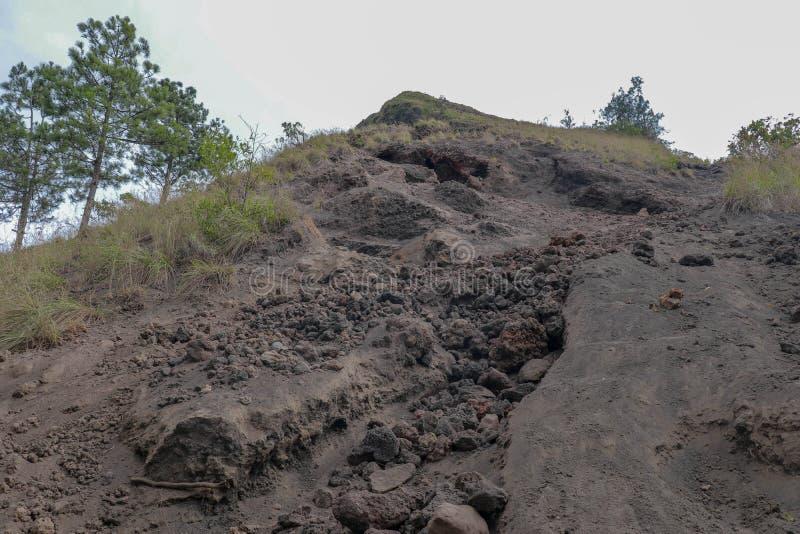 Rastro polvoriento con escoria de la lava y rocas al top del volcán de Batur Terreno extremo del camino a la montaña Sendero alre fotografía de archivo
