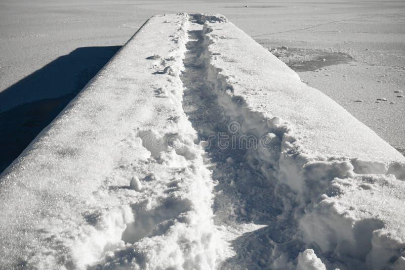 Rastro que camina en una pasarela nevosa en un lago congelado Jasna, Kranjska Gora, Eslovenia imagenes de archivo