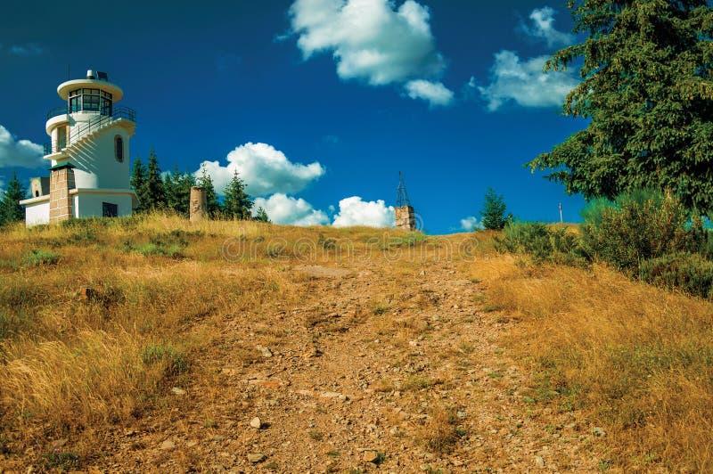 Rastro rocoso que va al faro encima de la colina imagenes de archivo