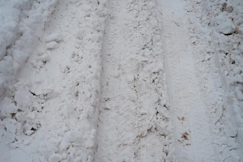 Rastros de ruedas en la nieve blanca Muchas impresiones de las ruedas de coches Venta de la nieve en invierno de un gran número foto de archivo