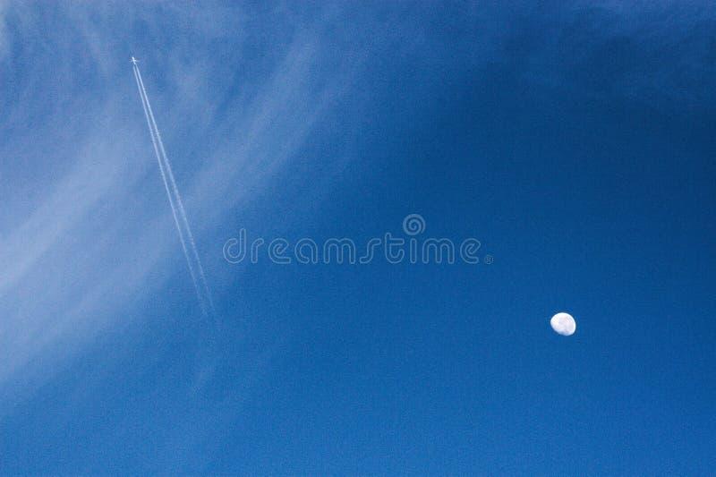 Rastros del avión y del vapor de reacción que rayan a través del cielo azul, luna de disminución apagado al lado imágenes de archivo libres de regalías