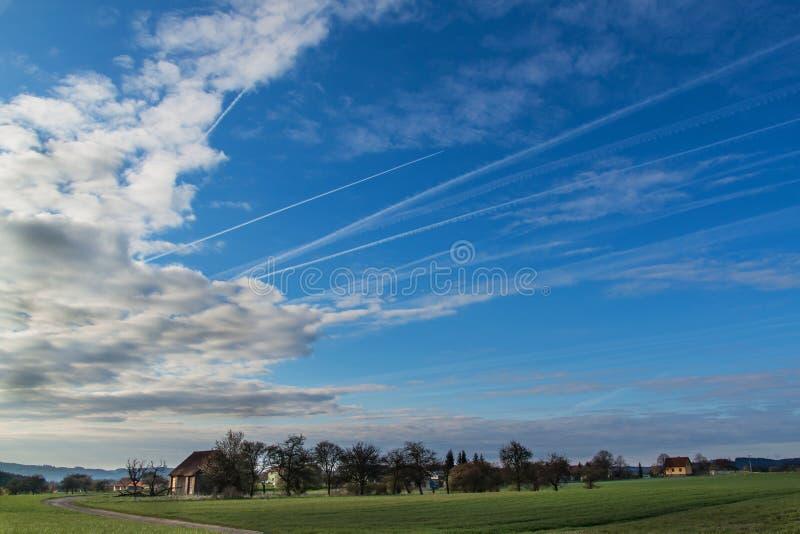 Rastros del cielo y de la condensación de la mañana de aviones Cielo de la primavera fotos de archivo