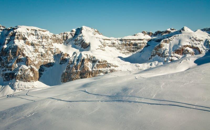 Rastros del esquí en nieve de la alta montaña imagenes de archivo