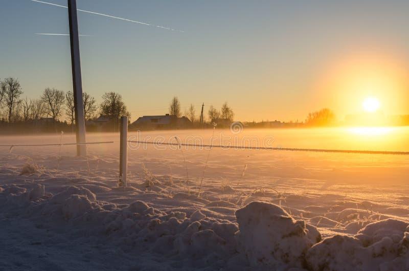 Rastros del jet y una puesta del sol de oro en un campo nevoso imágenes de archivo libres de regalías