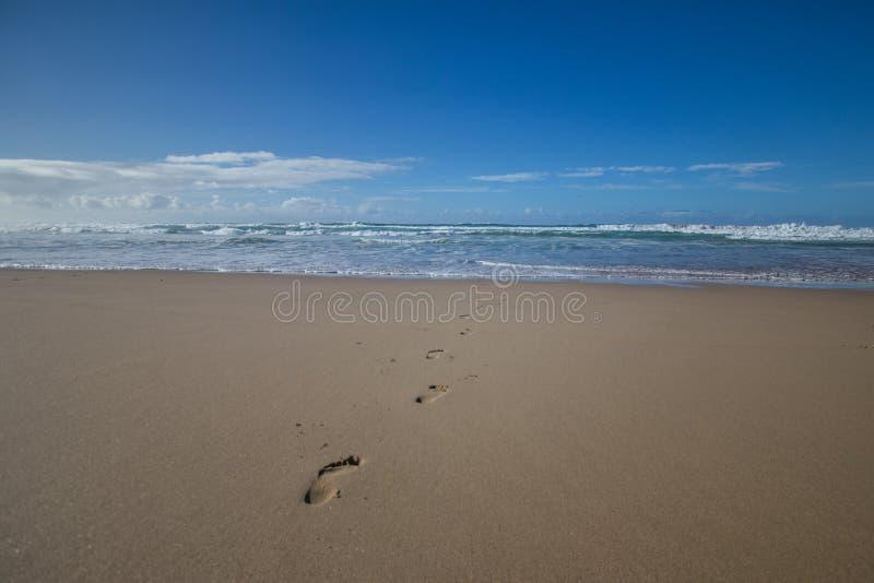 Rastros del pie de la arena foto de archivo