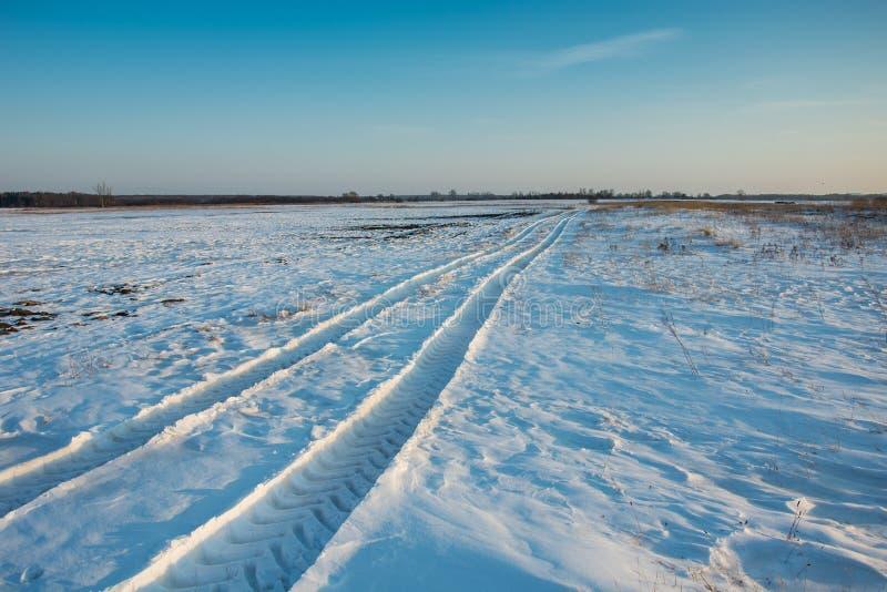 Rastros del vehículo en la nieve hacia el horizonte imagenes de archivo