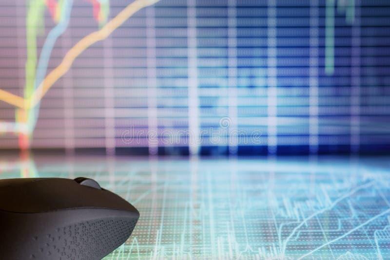 Ratón del ordenador en la exhibición futurista con los gráficos del mercado de acción imagenes de archivo
