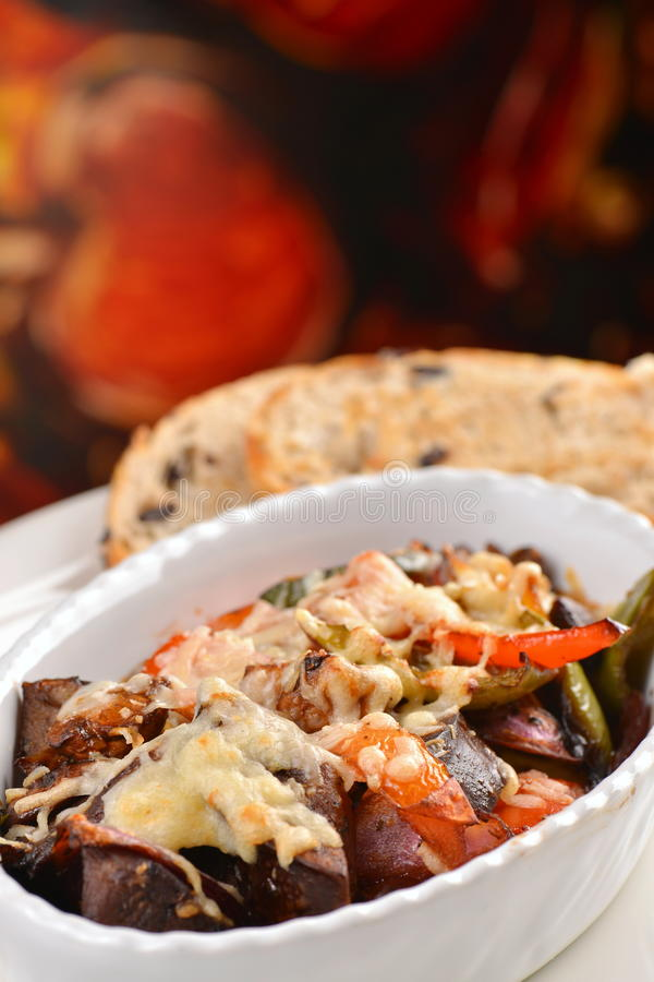 Ratatouille baked in the oven. With a cheese and olives bread stock image