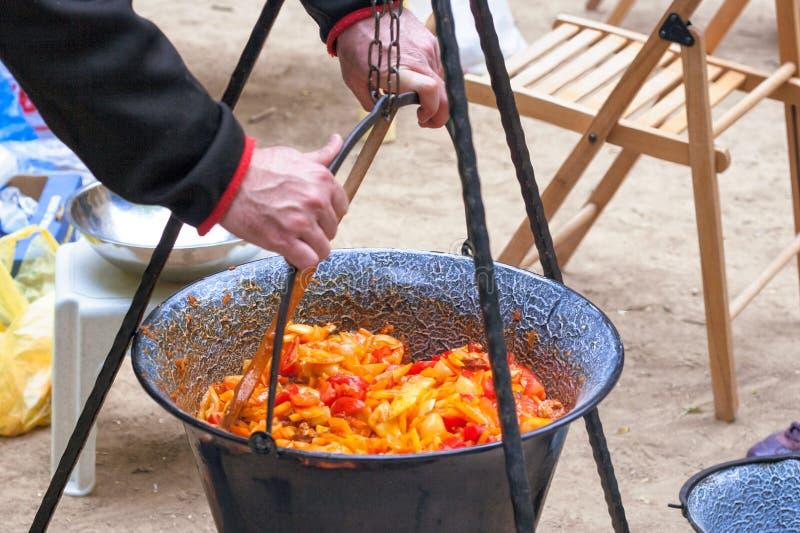 Ratatouille in a cauldron. Making hungarian ratatouille in a cauldron on a campfire stock image