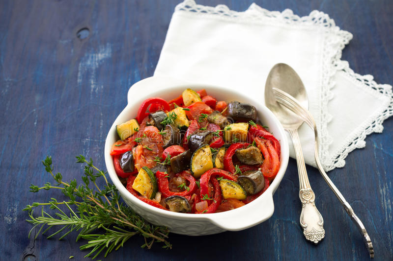 Ratatouille on a dark blue background. Ratatouille, a traditional French dish of fresh vegetables in a white ceramic bowl on a dark blue background royalty free stock photos