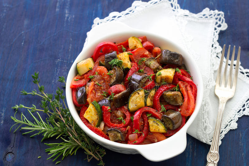 Ratatouille on a dark blue background. Ratatouille, a traditional French dish of vegetables in a white ceramic bowl on a dark blue background, selective focus stock photos