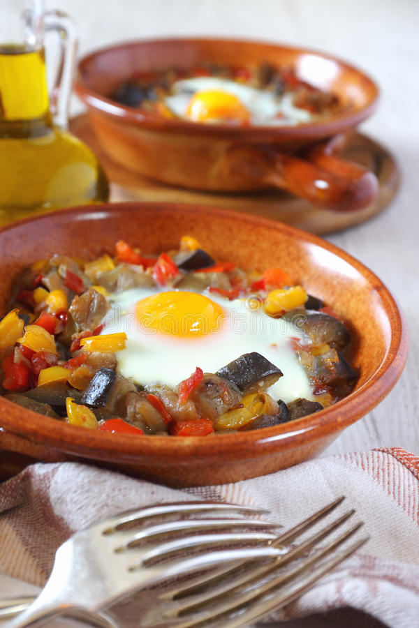 Ratatouille with stewed in oven egg in two ceramic plates and olive oil & Ratatouille With Egg In Two Ceramic Plates Stock Photo - Image of ...
