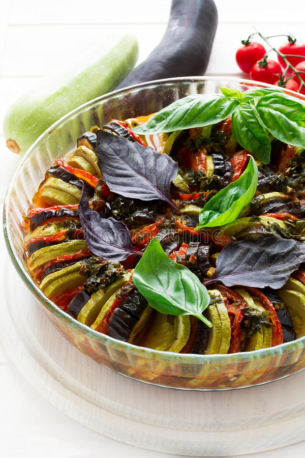 Ratatouille with eggplants, tomatoes and zucchini decorated basil leaves. On white wooden background royalty free stock photography