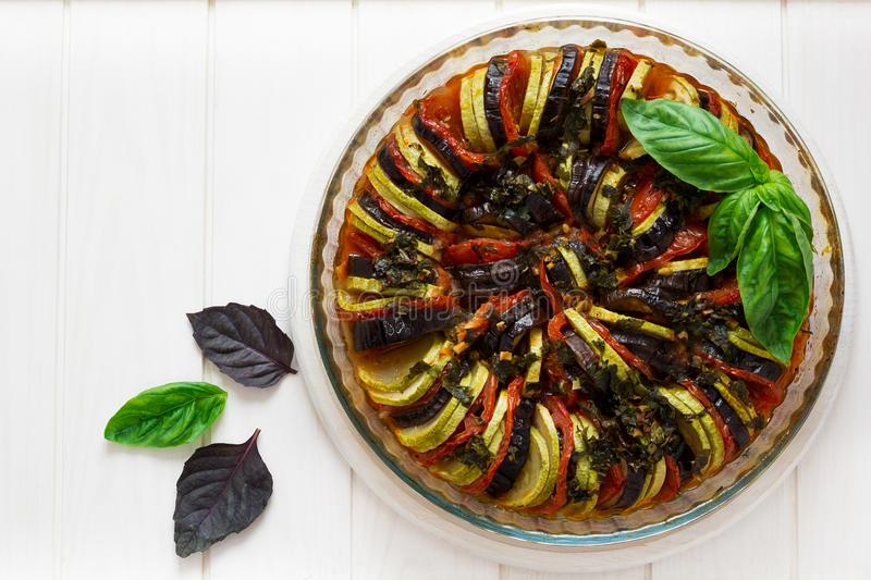 Ratatouille with eggplants, tomatoes and zucchini decorated basil leaves. On white wooden background royalty free stock photo
