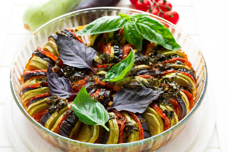 Ratatouille with eggplants, tomatoes and zucchini decorated basil leaves. On white wooden background stock photography