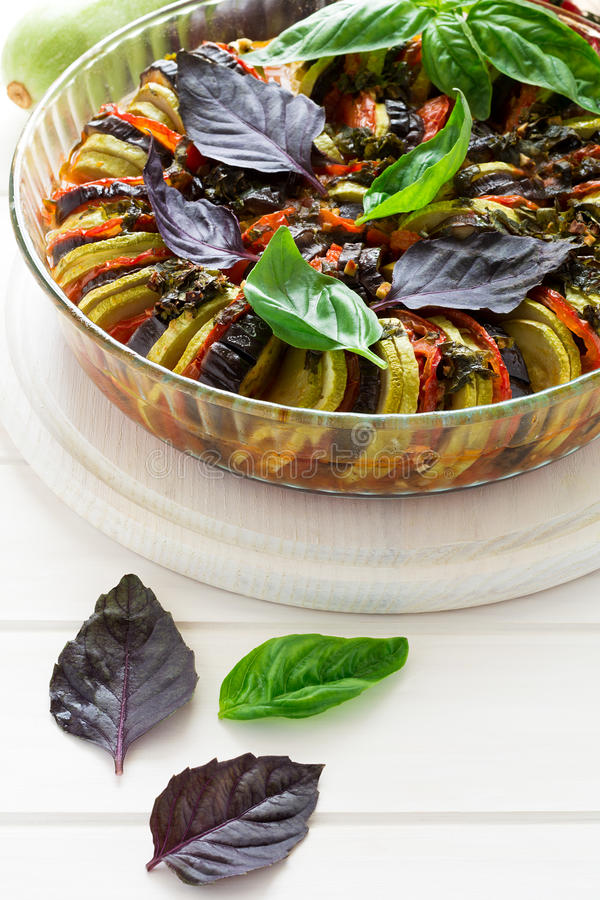 Ratatouille with eggplants, tomatoes and zucchini decorated basil leaves. On white wooden background royalty free stock image