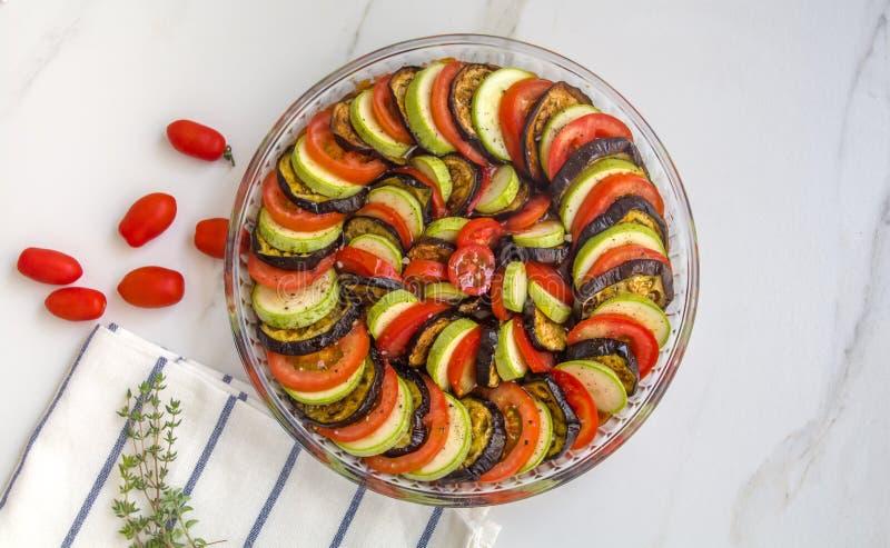 Ratatouille: Färgrika lager av nya sommargrönsaker: zucchini, aubergine, tomater på säsong för tomatsås med vitlök och fres arkivfoto