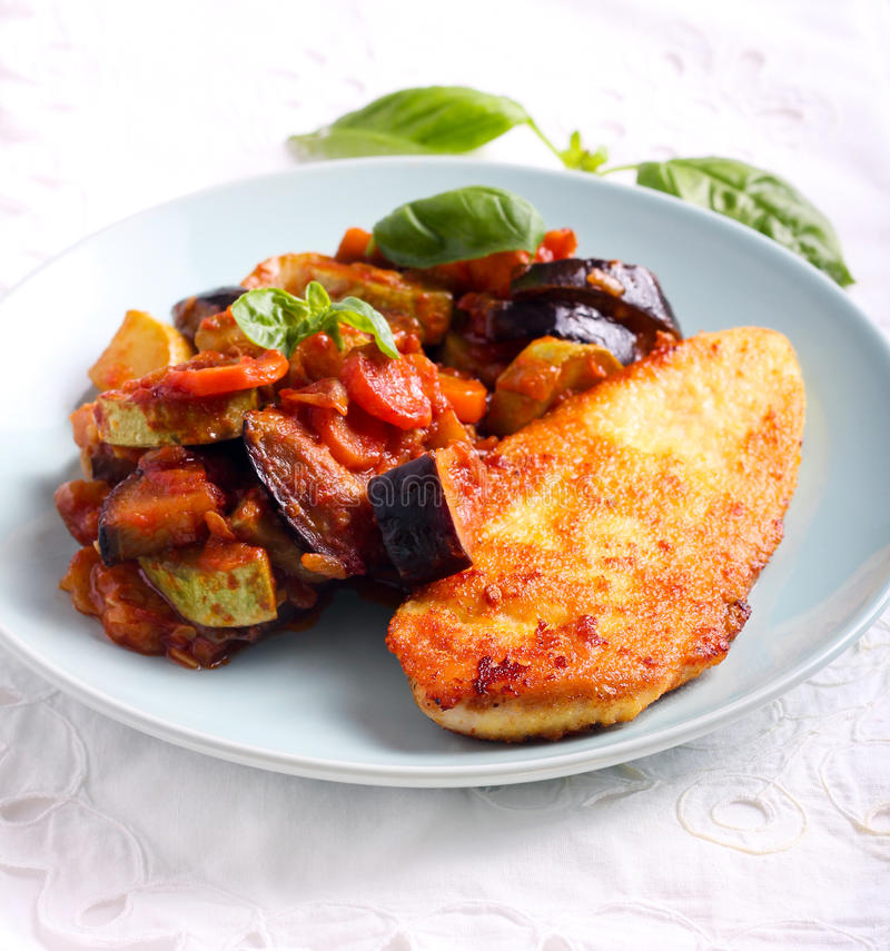 Ratatouille and spiced fried chicken breast. On plate stock photos