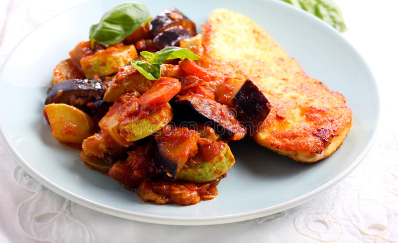 Ratatouille and spiced fried chicken breast. On plate stock photo