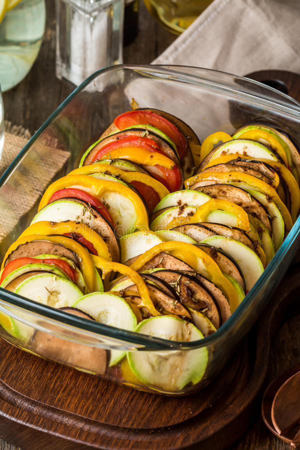 Ratatouille - traditional French Provencal vegetable dish. In glass brazier on wooden cutting board royalty free stock images