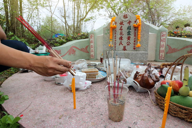 Ratchaburi,泰国- 2017年4月4日:崇拜与牺牲提供的泰国人祈祷的祖先在Qingming节日 库存照片
