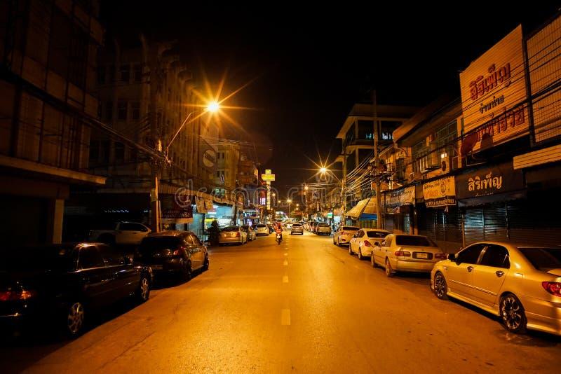 Ratchaburi, Tailândia: 17 de janeiro de 2014 - paisagem da baixa na noite na área rural Imagem da perspectiva da rua local em foto de stock royalty free
