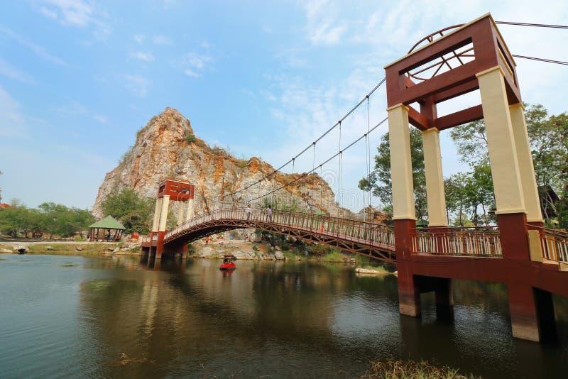 Ratchaburi, Tailândia - 10 de março de 2018: Ponte sobre o lago da água do parque da pedra de Ngu do khao foto de stock