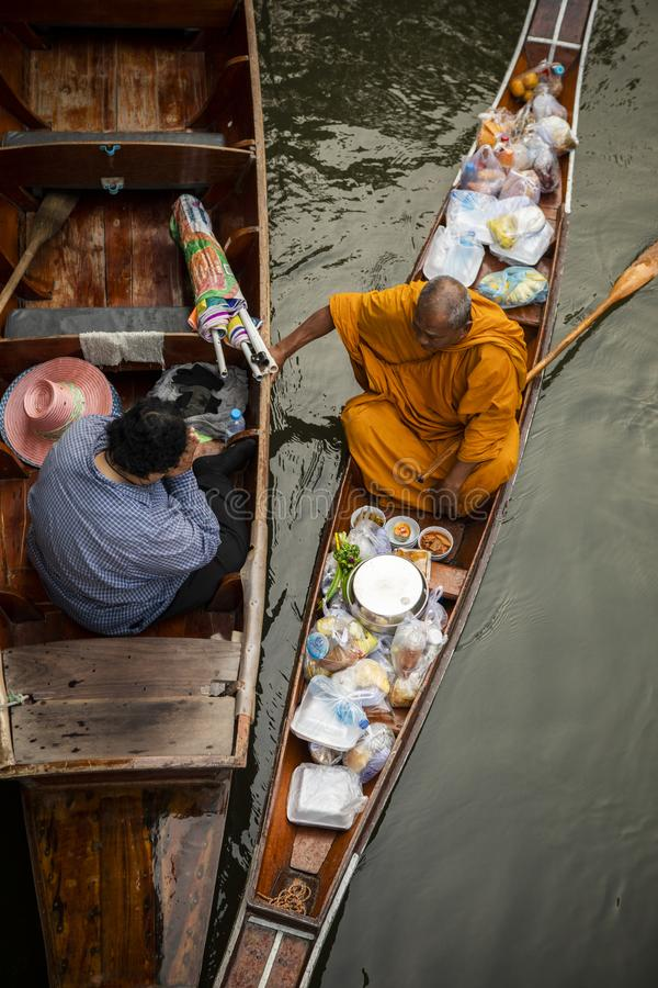 Ratchaburi Tailândia - january12,2019: monge tailandesa que recebe o alimento da mulher tailandesa que oferece no canal um do sad imagem de stock royalty free
