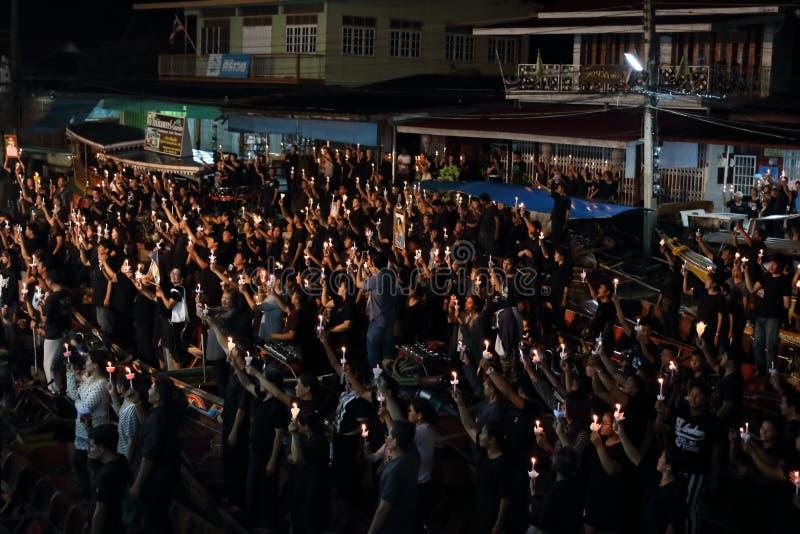 Ratchaburi, Tailandia - octubre 29,2016: La gente tailandesa que canta el himno y lleva a cabo las velas en el barco ruega para s imágenes de archivo libres de regalías