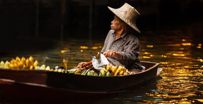 Ratchaburi, Thailand - April 28, 2018: de fruittuinman, koopvaardijhandelaar roeit boot om opbrengst aan toeristen te verkopen, D stock fotografie
