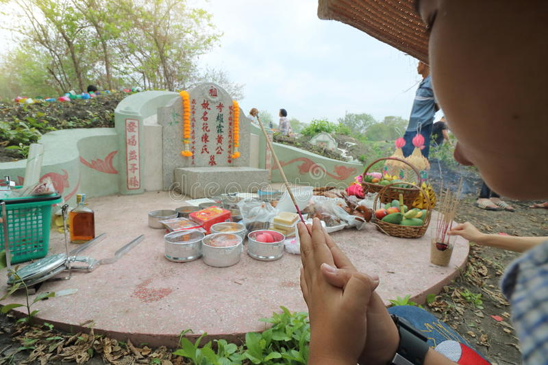 Ratchaburi, Thailand - April 4, 2017 : Thai people praying Ancestor Worshipping. With Sacrificial offering in the Qingming Festival or Tomb sweeping day at Jing royalty free stock image
