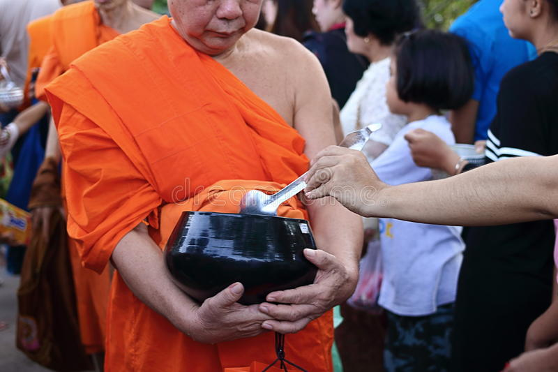 Ratchaburi, Thailand - 14. April 2017: Thailändische Leute setzen Lebensmittelangebote in einen Mönch ein, ` s, das Almosen an So lizenzfreies stockfoto