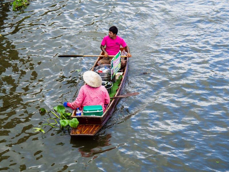 RATCHABURI, THAILAND - JAN 21, 2016 ,Asian woman and men on small boat selling food at Damnoen Saduak floating market royalty free stock images