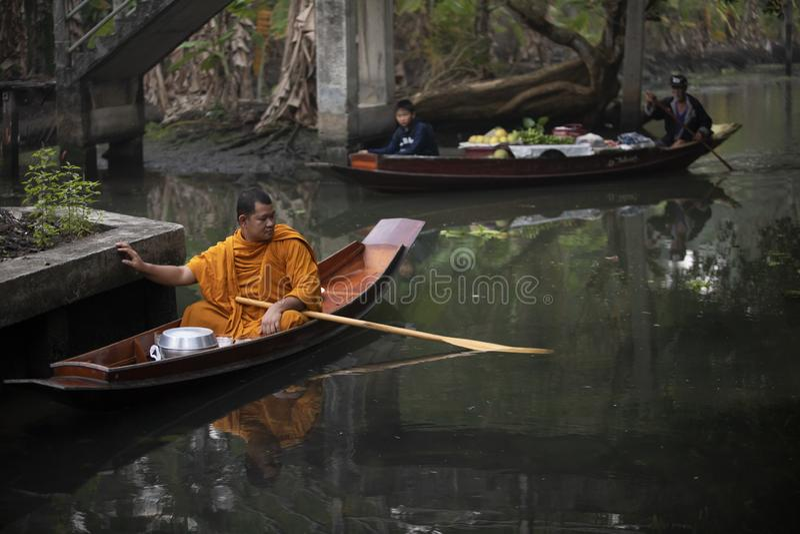 Ratchaburi thailand - january11,2019 : thai monk sailing wood boat in narrow canal on dumneon saduak district in ratchaburi for royalty free stock photos