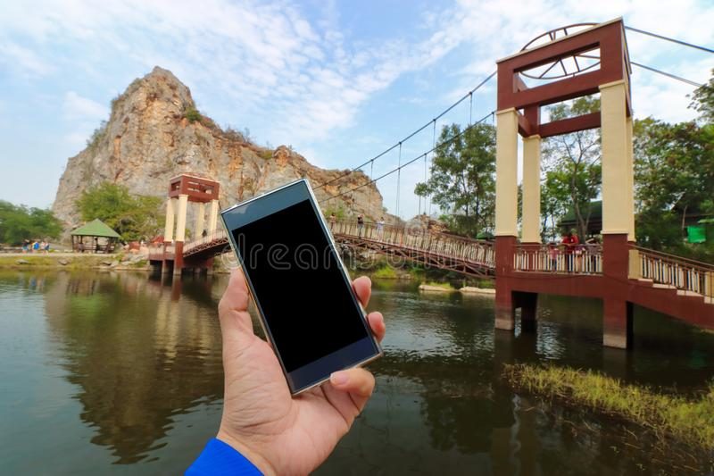 Ratchaburi , Thailand - March 10 , 2018 : Hands of unidentified holding mobile smart phone with bridge over water lake of khao Ngu stock photography